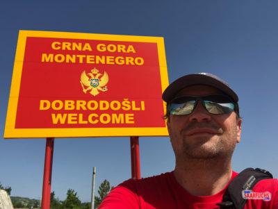 Saarfuchs vor dem Willkommens-Schild an der Grenze zu Montenegro